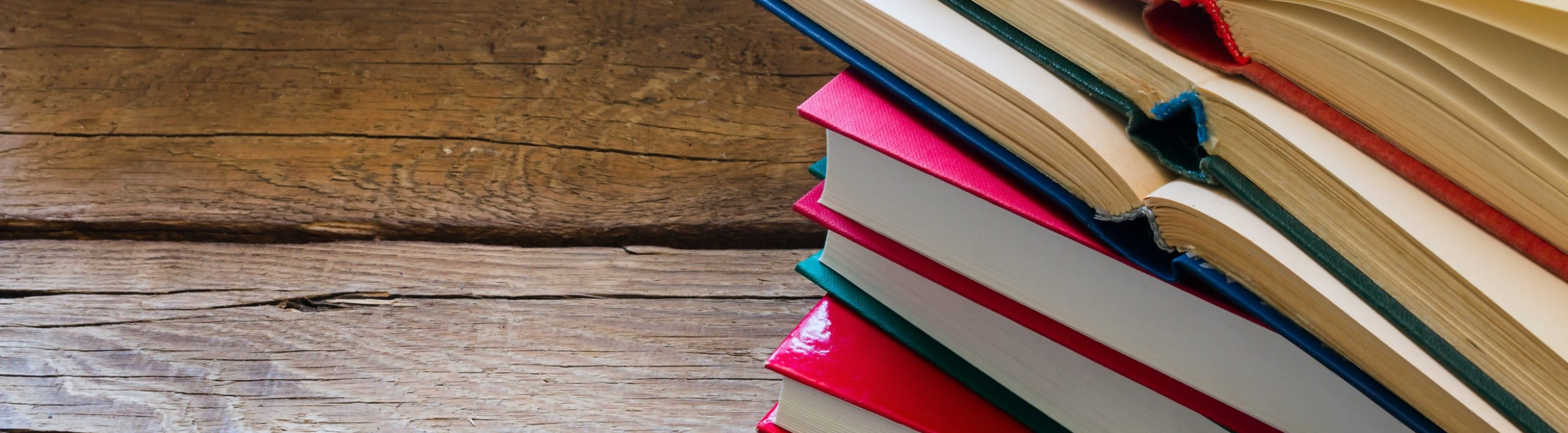 Open book on a stack of closed books with space for text